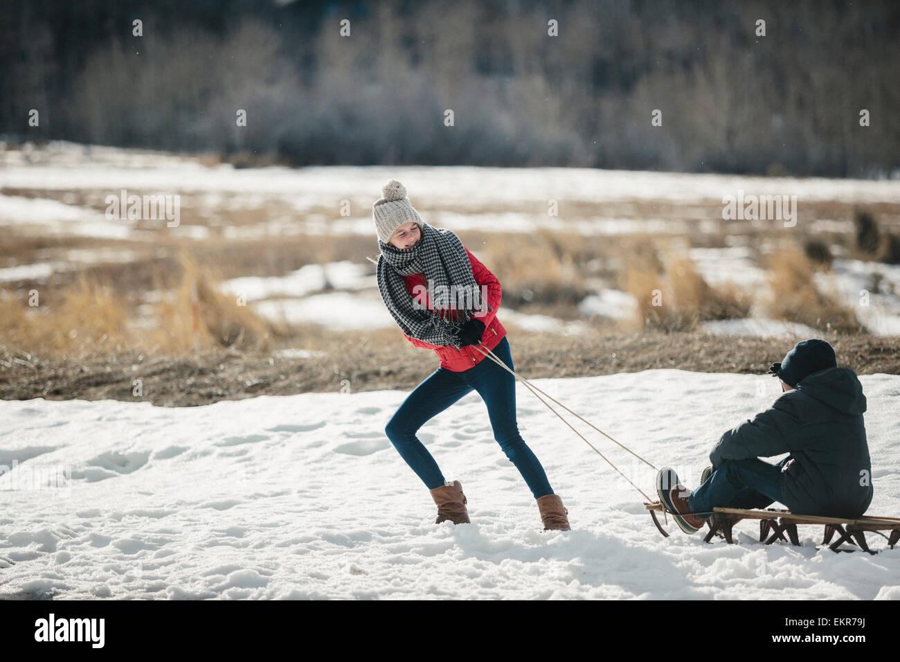 Un fratello e una sorella nella neve, uno tirando l'altro su di una slitta. Immagini Stock