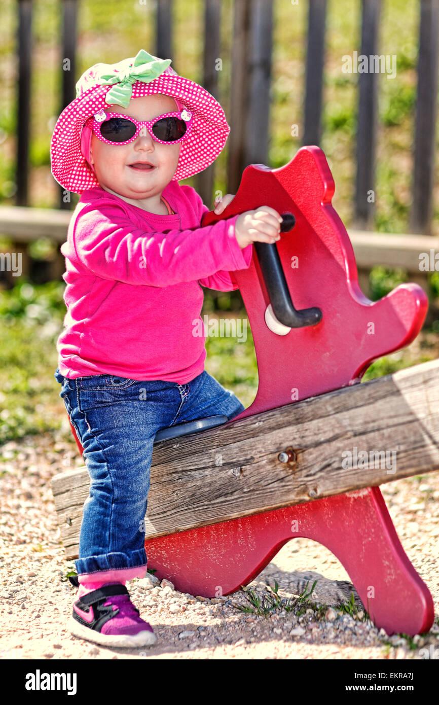 Una graziosa bambina con gli occhiali rosa e hat divertendosi Immagini Stock