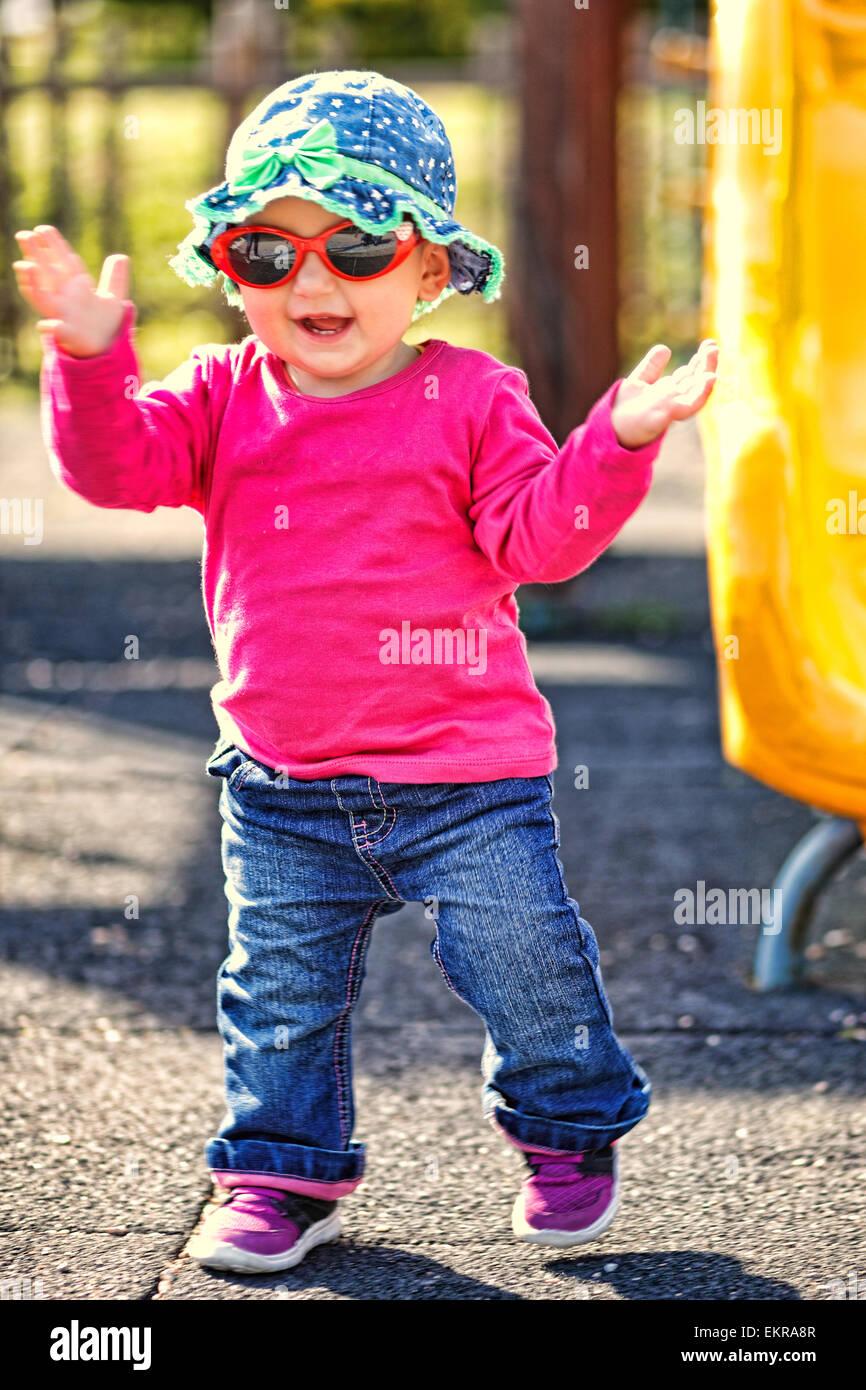 Una graziosa bambina con gli occhiali rossi e blu hat divertendosi Immagini Stock