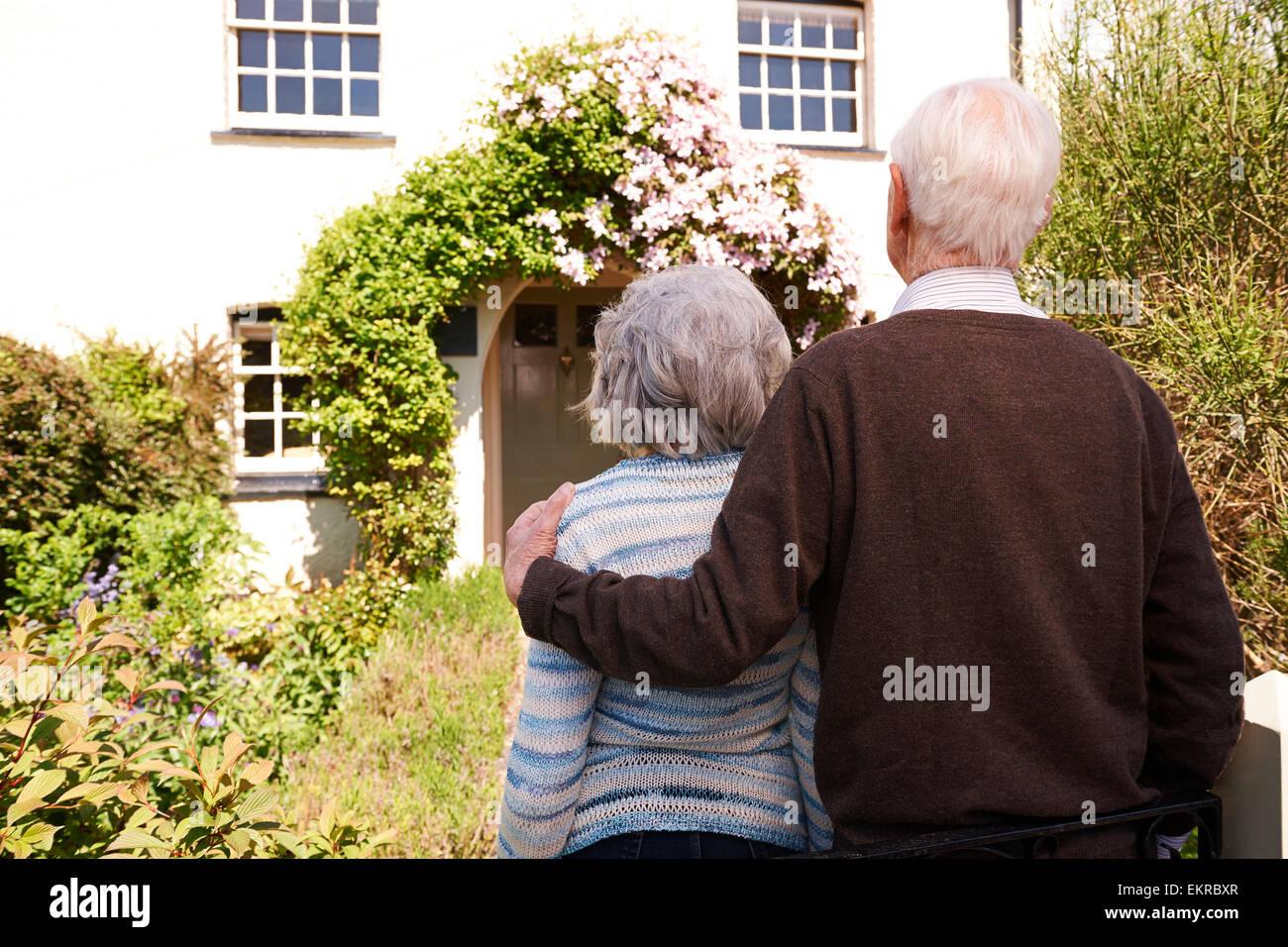 Vista posteriore della coppia Senior al di fuori del grazioso cottage Immagini Stock