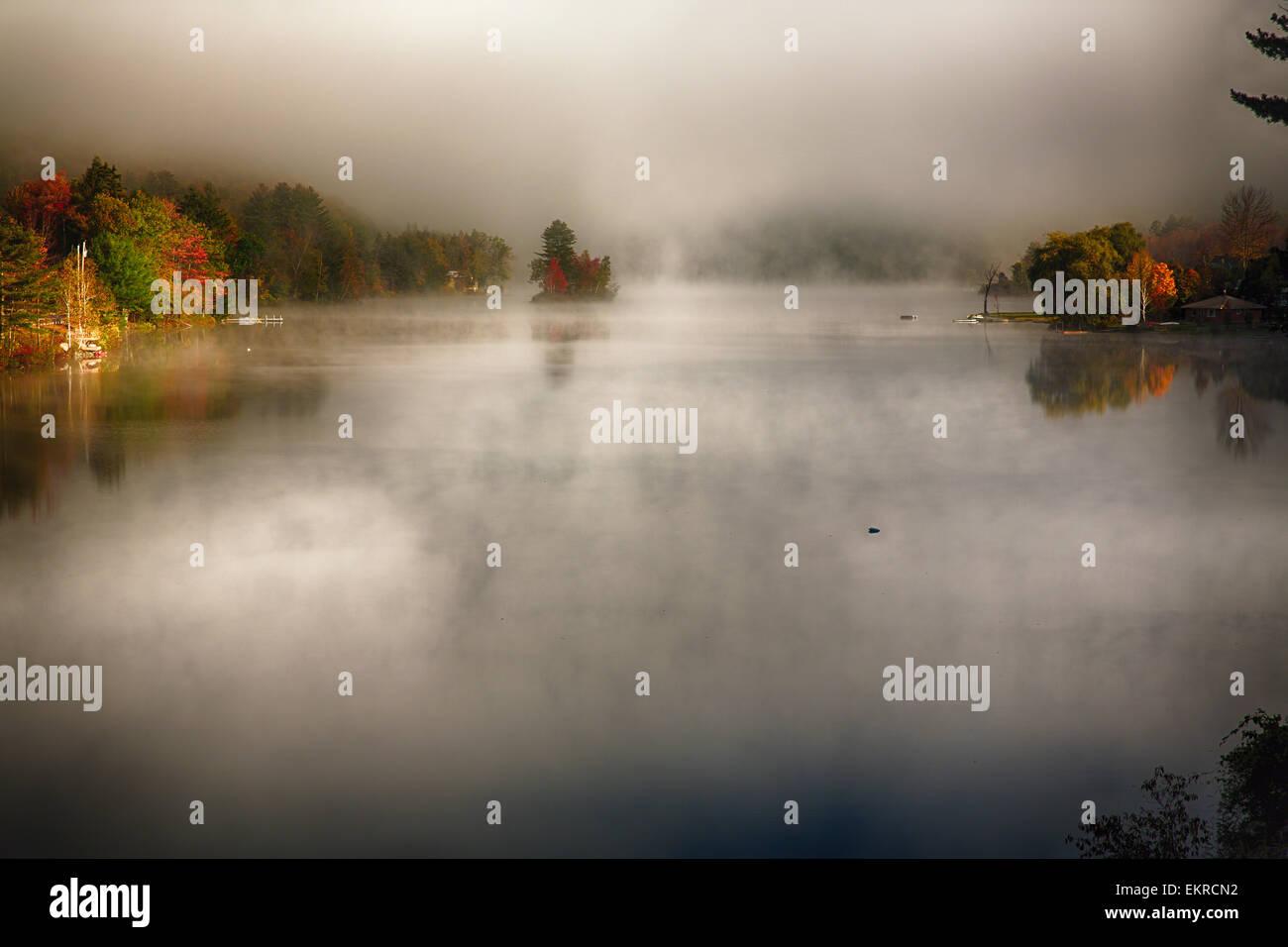 Angolo di Alta Vista di un lago con nebbia di mattina durante la caduta, Knapp Brook Pond, Vermont Immagini Stock
