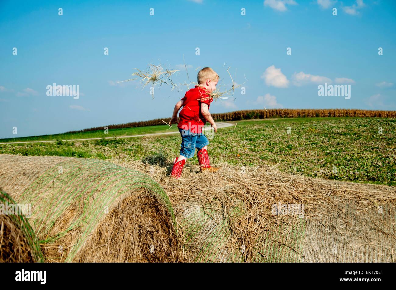 Ragazzo camminando sul haybales Immagini Stock