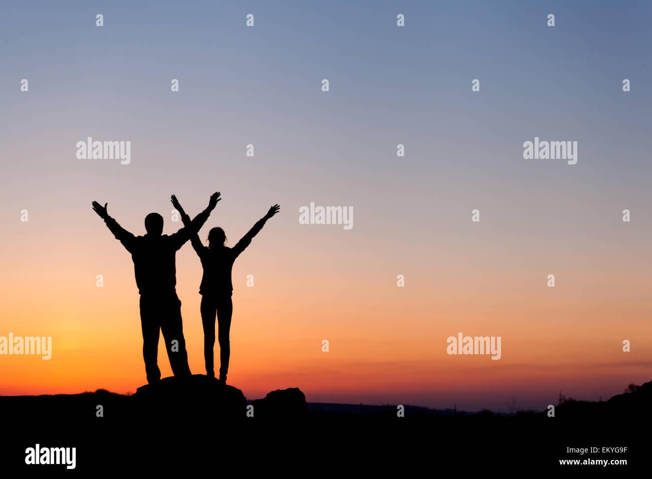 Silhouette di felicità famiglia con bracci sollevati fino contro il bellissimo cielo colorati. Tramonto d'estate. Immagini Stock