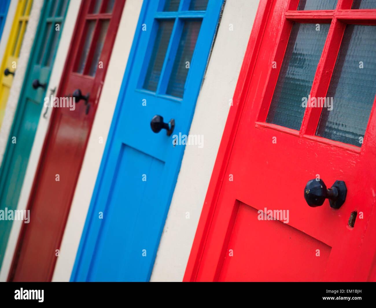 Una fila di porte dipinte in colori luminosi presso la località balneare di North Berwick, in Scozia. Immagini Stock