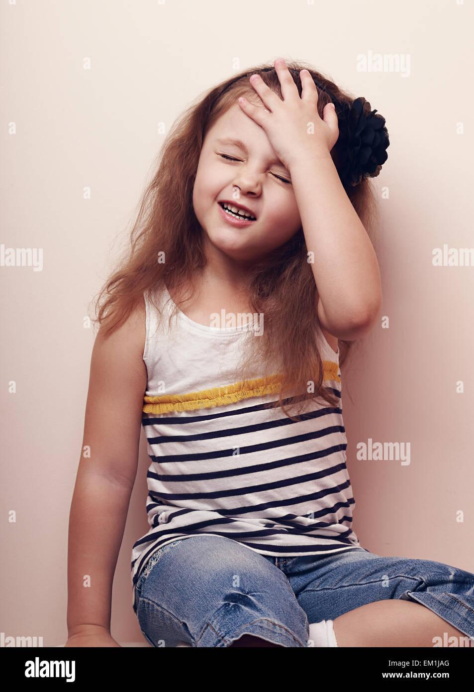 Deluso kid ragazza pensando con la mano sulla testa. Ritratto a colori Immagini Stock