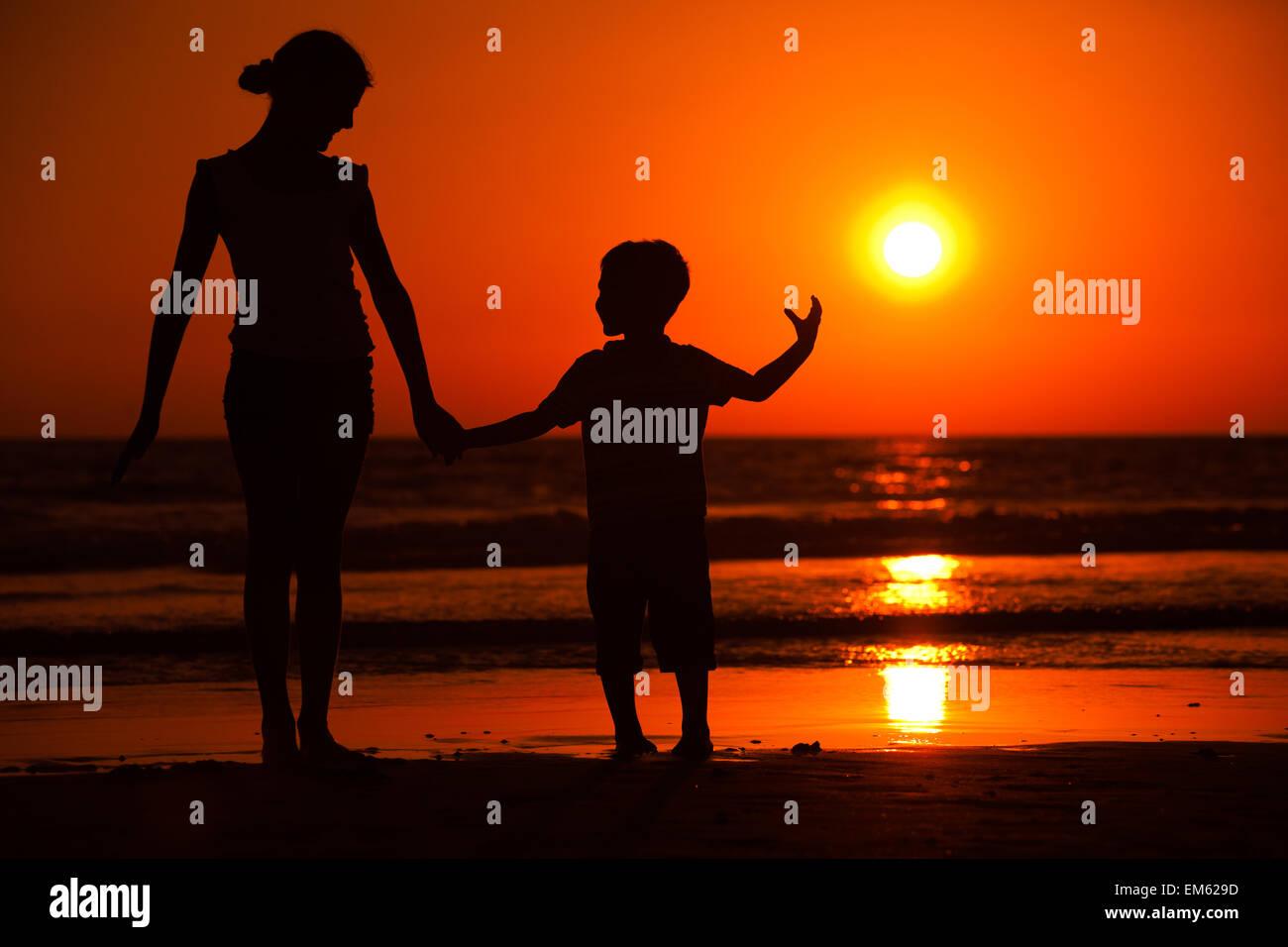 Sunset silhouette di piccolo fratello e sorella Immagini Stock