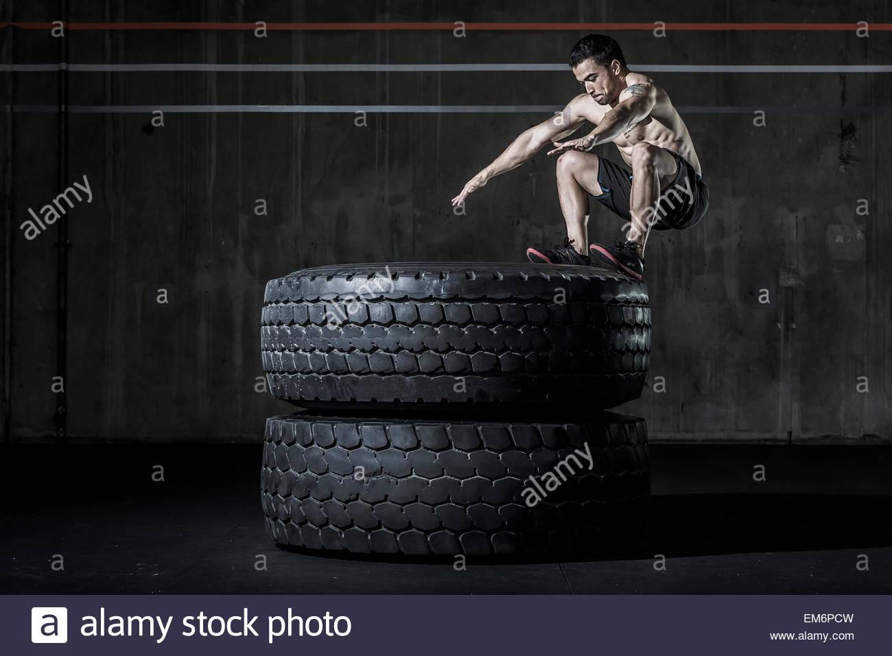 Un maschio shirtless weightlifter e atleta CrossFit eseguendo una scatola saltare sui due pneumatici in una palestra Immagini Stock