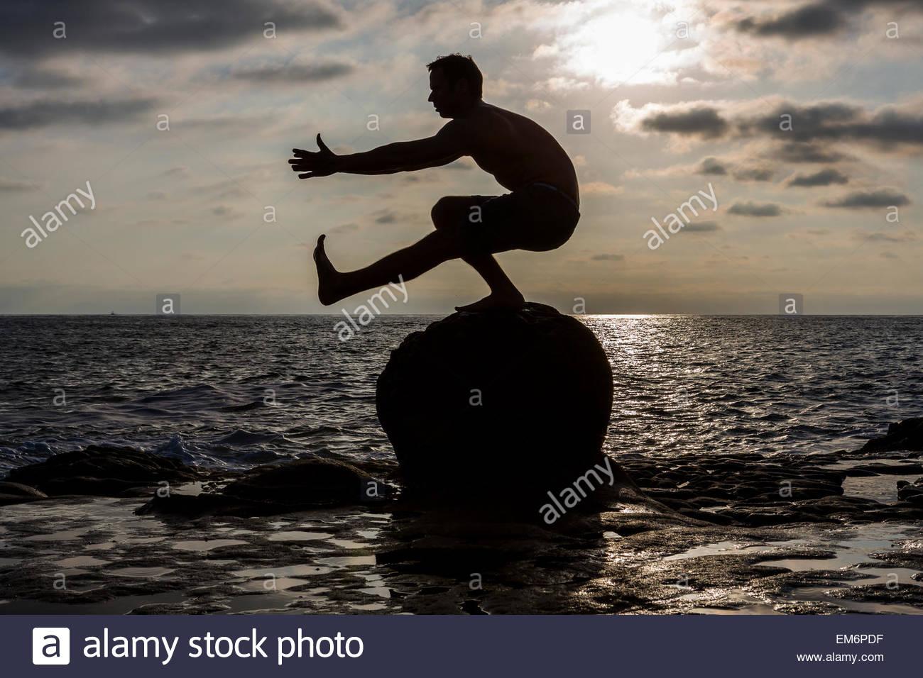La silhouette di un maschio shirtless CrossFit atleta come egli esegue una pistola o uno-gambe squat su una roccia Immagini Stock
