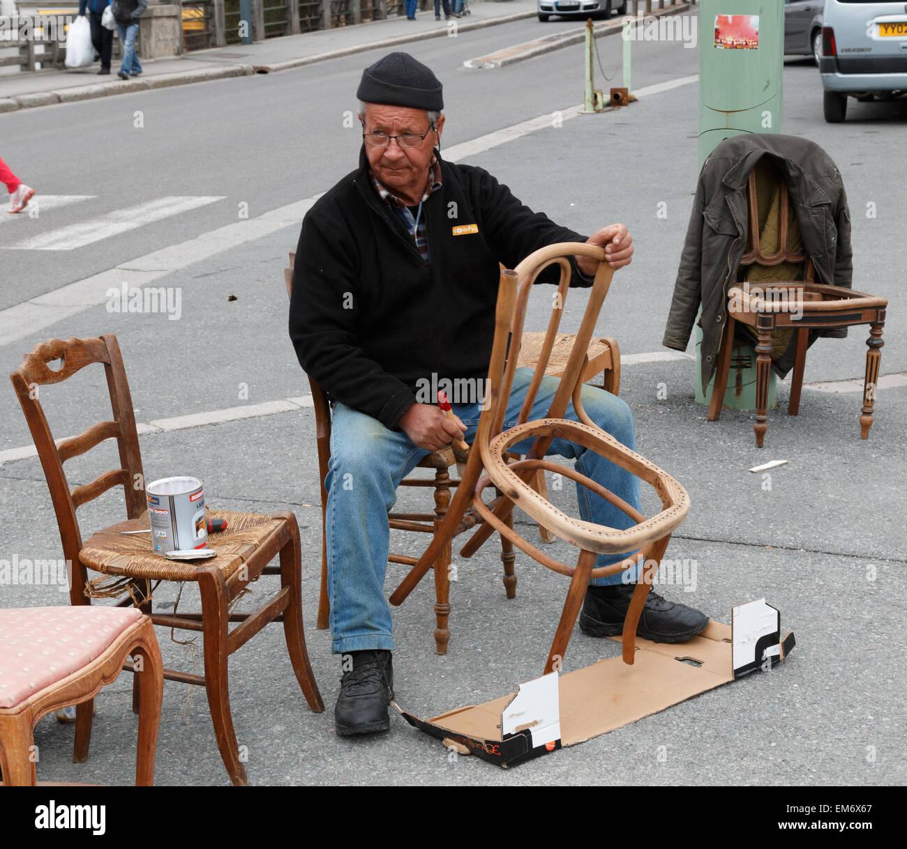Anziani, maschi Restauratore riparatore lavorando su una vecchia sedia. Egli è la pittura per la rimozione Immagini Stock
