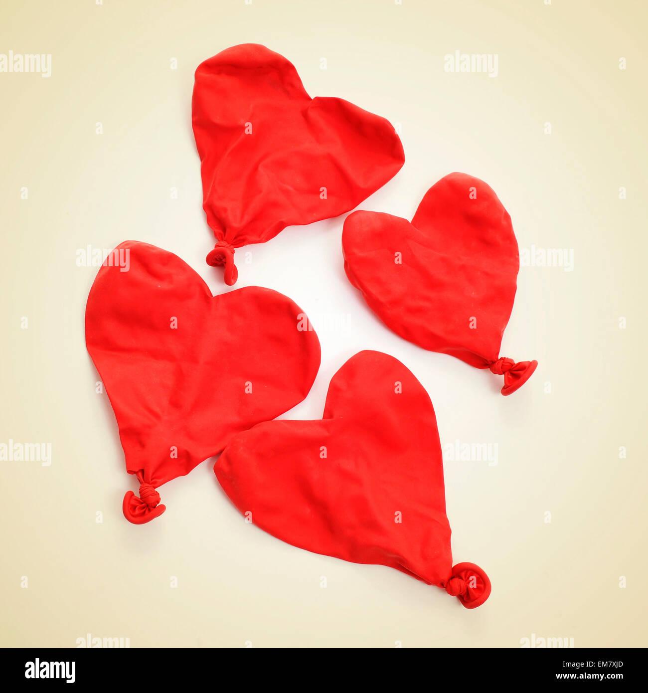 Alcuni sgonfiato heart-shaped balloons su uno sfondo beige, con un effetto retrò Immagini Stock