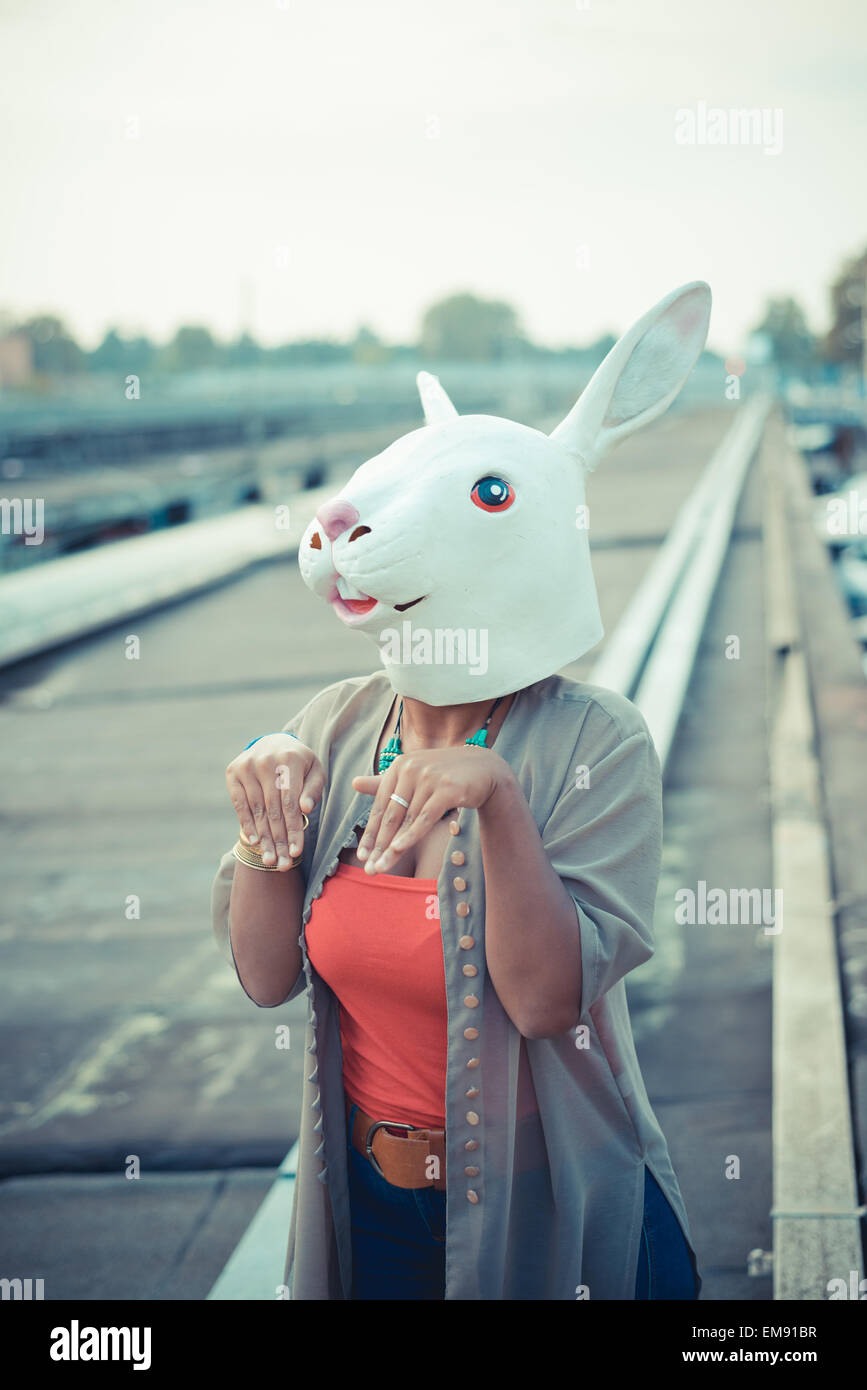 Giovane donna in costume di coniglio maschera in città area industriale Immagini Stock