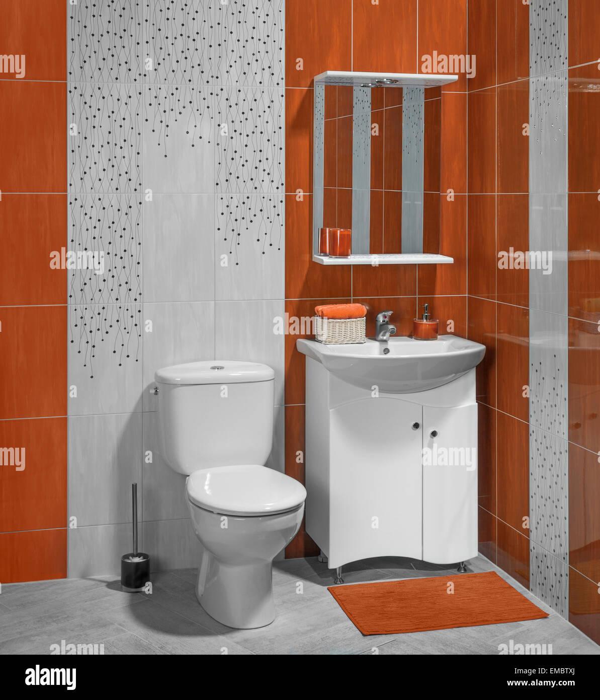 Splendidi interni di bagno con lavandino e wc decorata con piastrelle di colore arancione foto - Bagno di colore ...