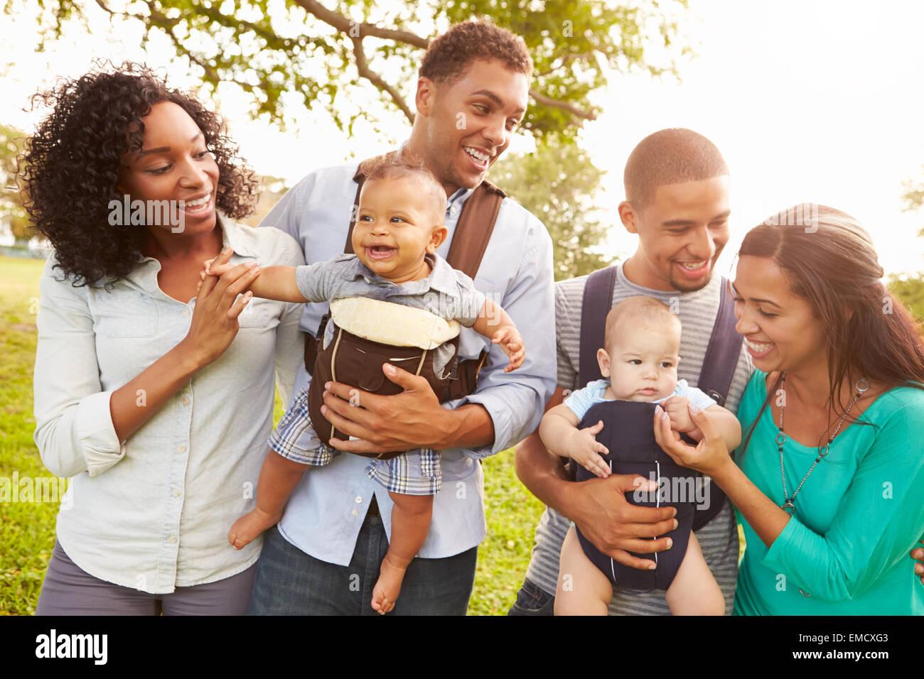 Due famiglie con Baby Carrier passeggiate nel parco Immagini Stock
