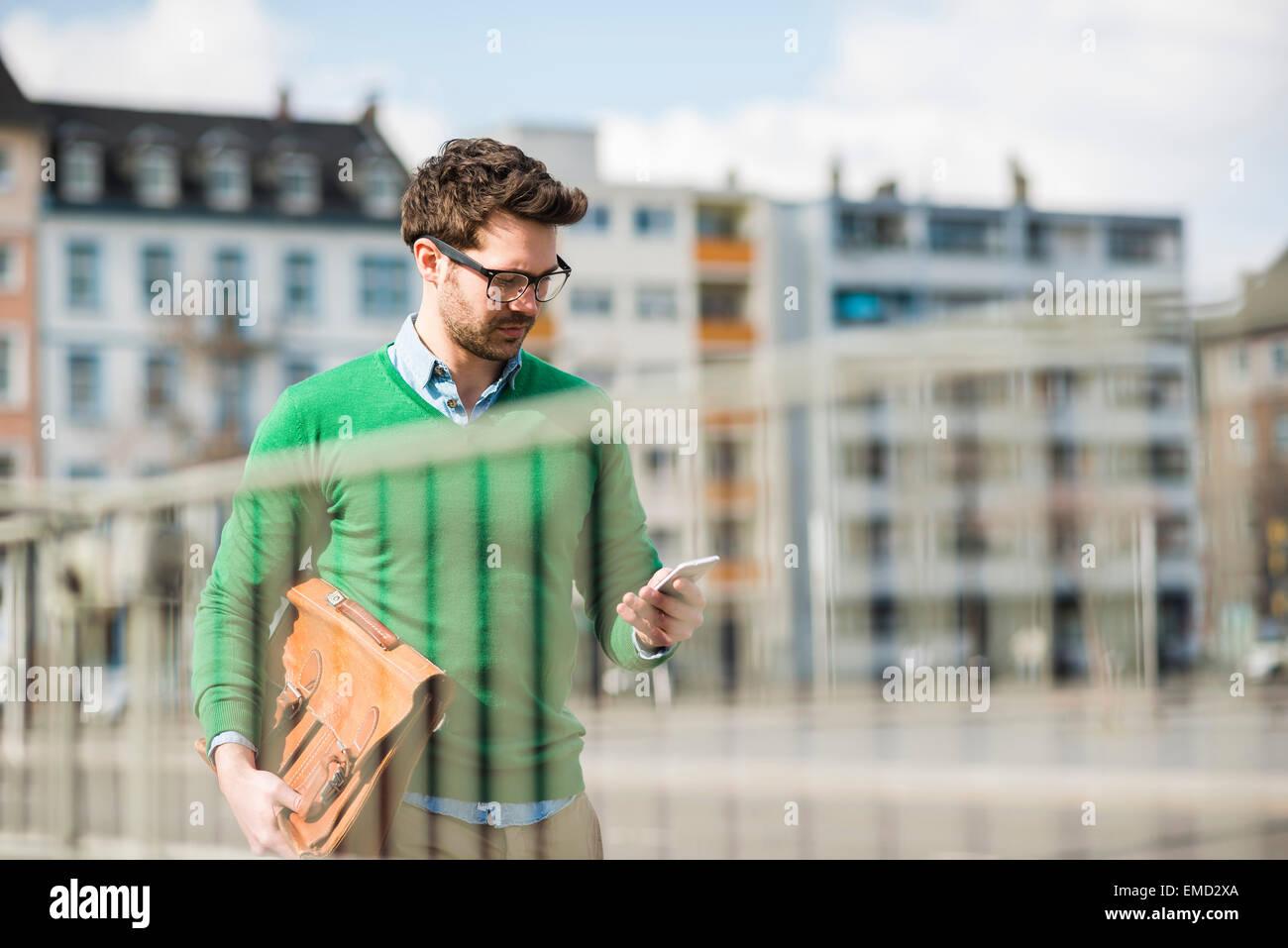 Uomo in maglione verde che porta nella valigetta, la lettura di un messaggio di testo Foto Stock