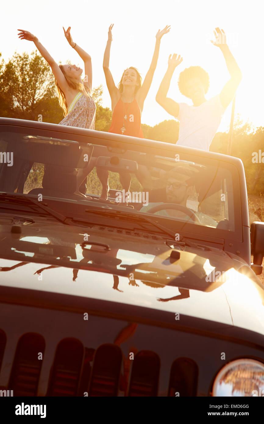 Tre donne che danzano nel retro della Open Top Car Immagini Stock