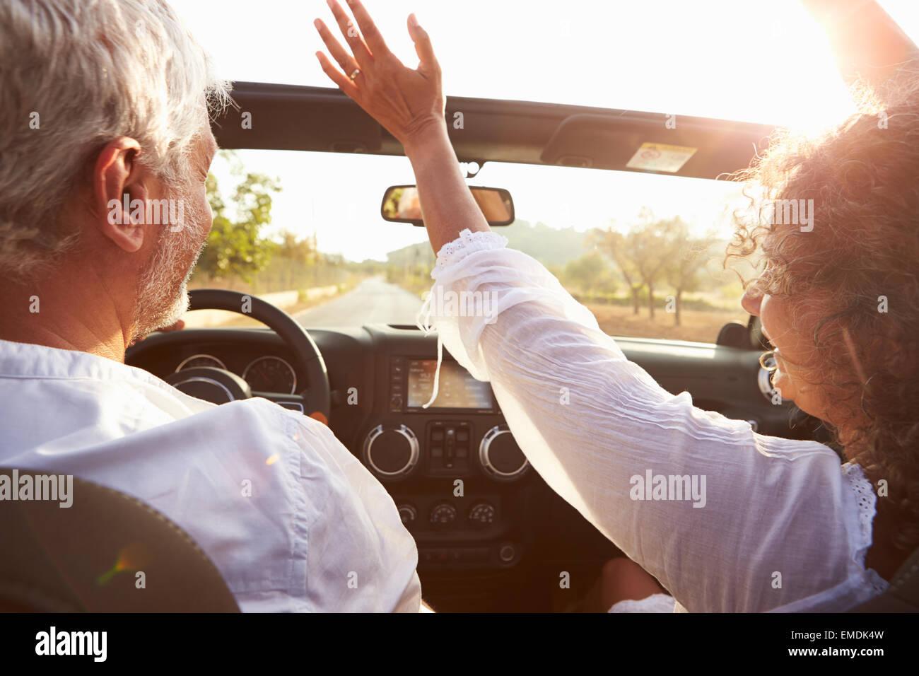 Coppia matura la guida lungo la strada di campagna in Open Top Car Immagini Stock