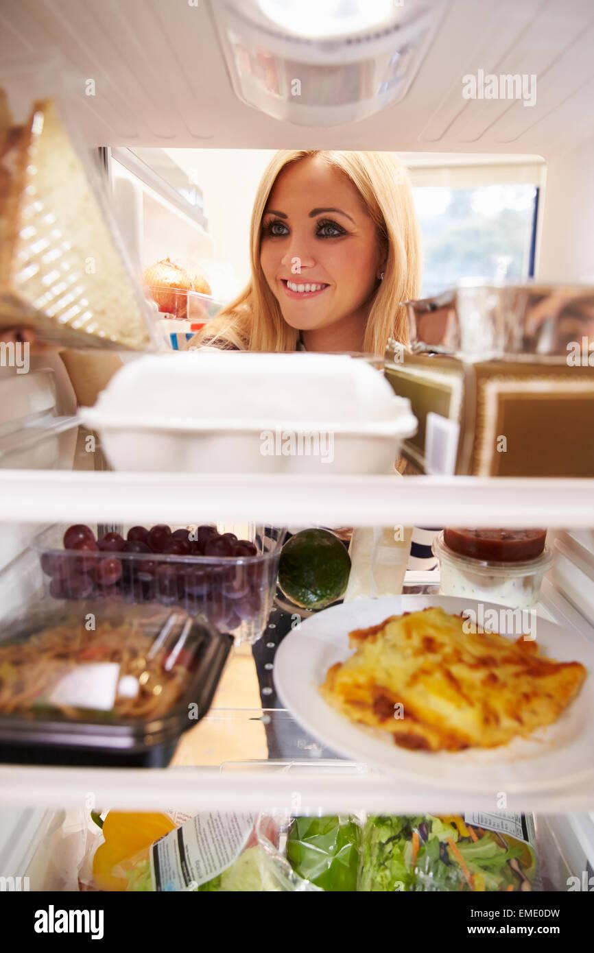 Donna che guarda all'interno del frigo di cibo e la scelta di sandwich Immagini Stock