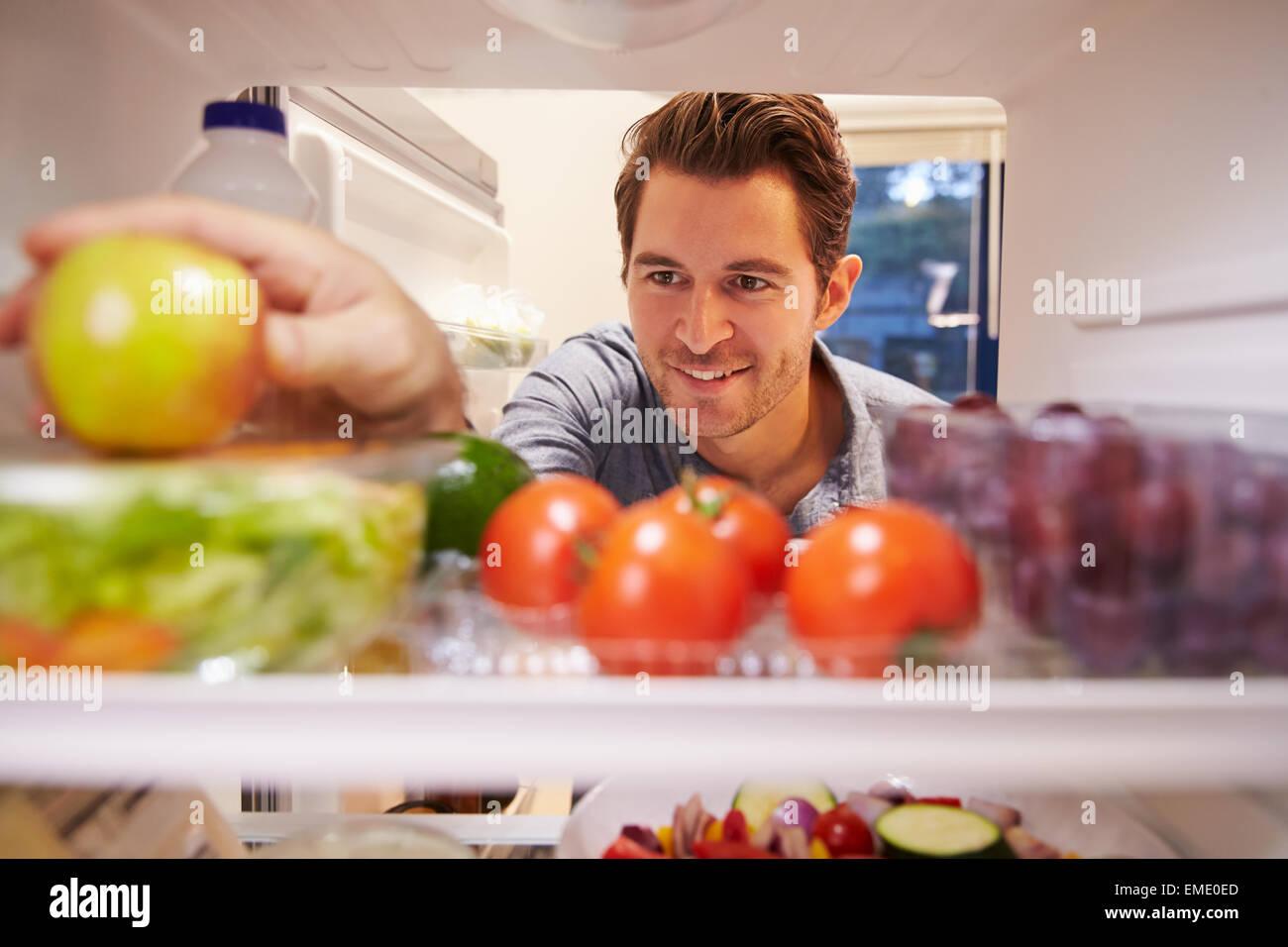 Uomo che guarda all'interno del frigo pieno di cibo e la scelta di Apple Immagini Stock