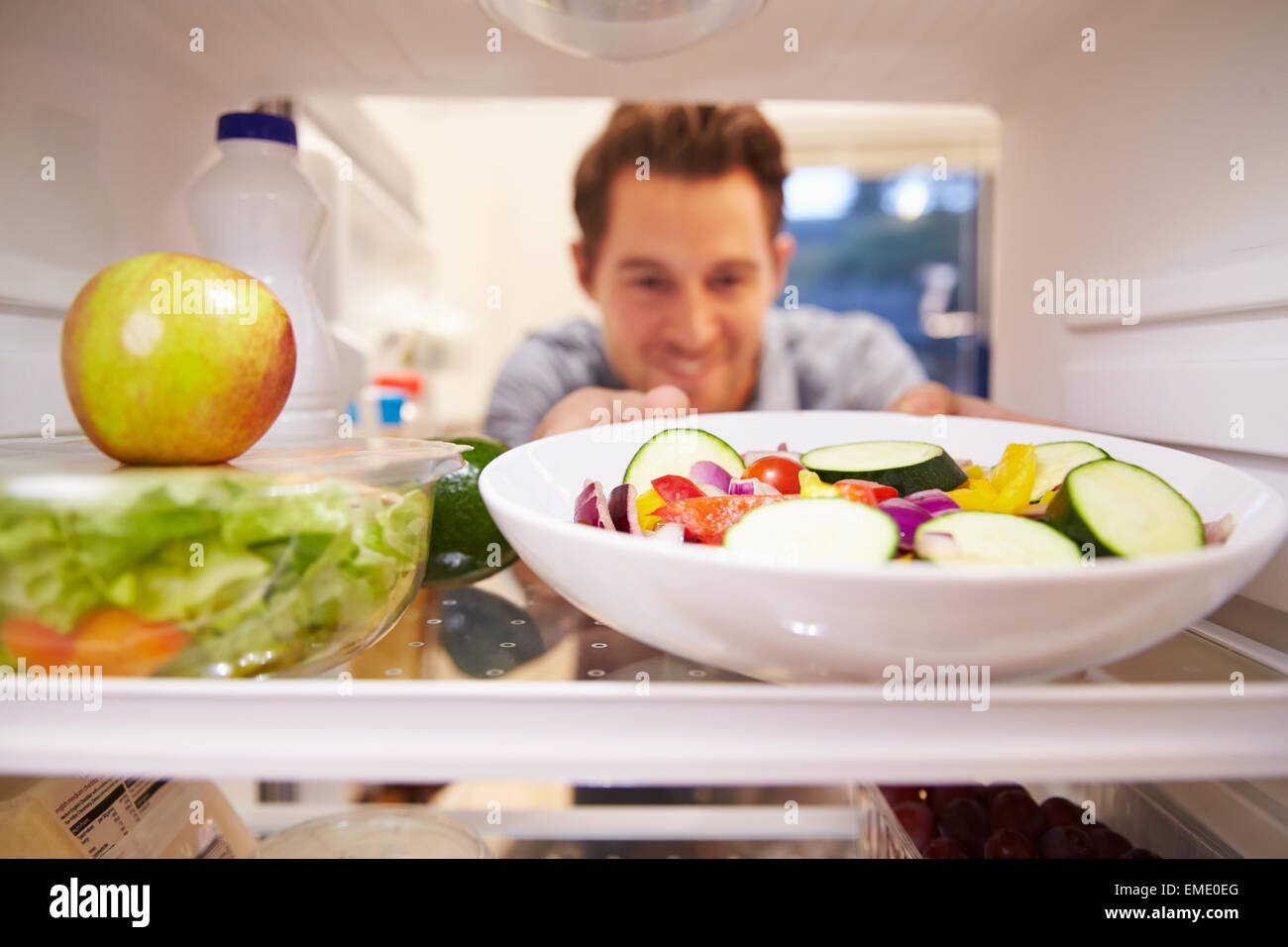 Uomo che guarda all'interno del frigo pieno di cibo e la scelta di insalate Immagini Stock