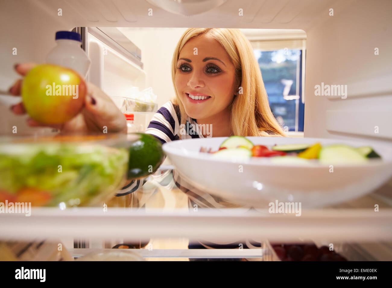 Donna che guarda all'interno del frigo pieno di cibo e la scelta di Apple Immagini Stock