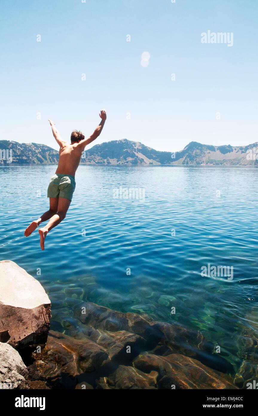Giovane uomo saltando nel lago Immagini Stock