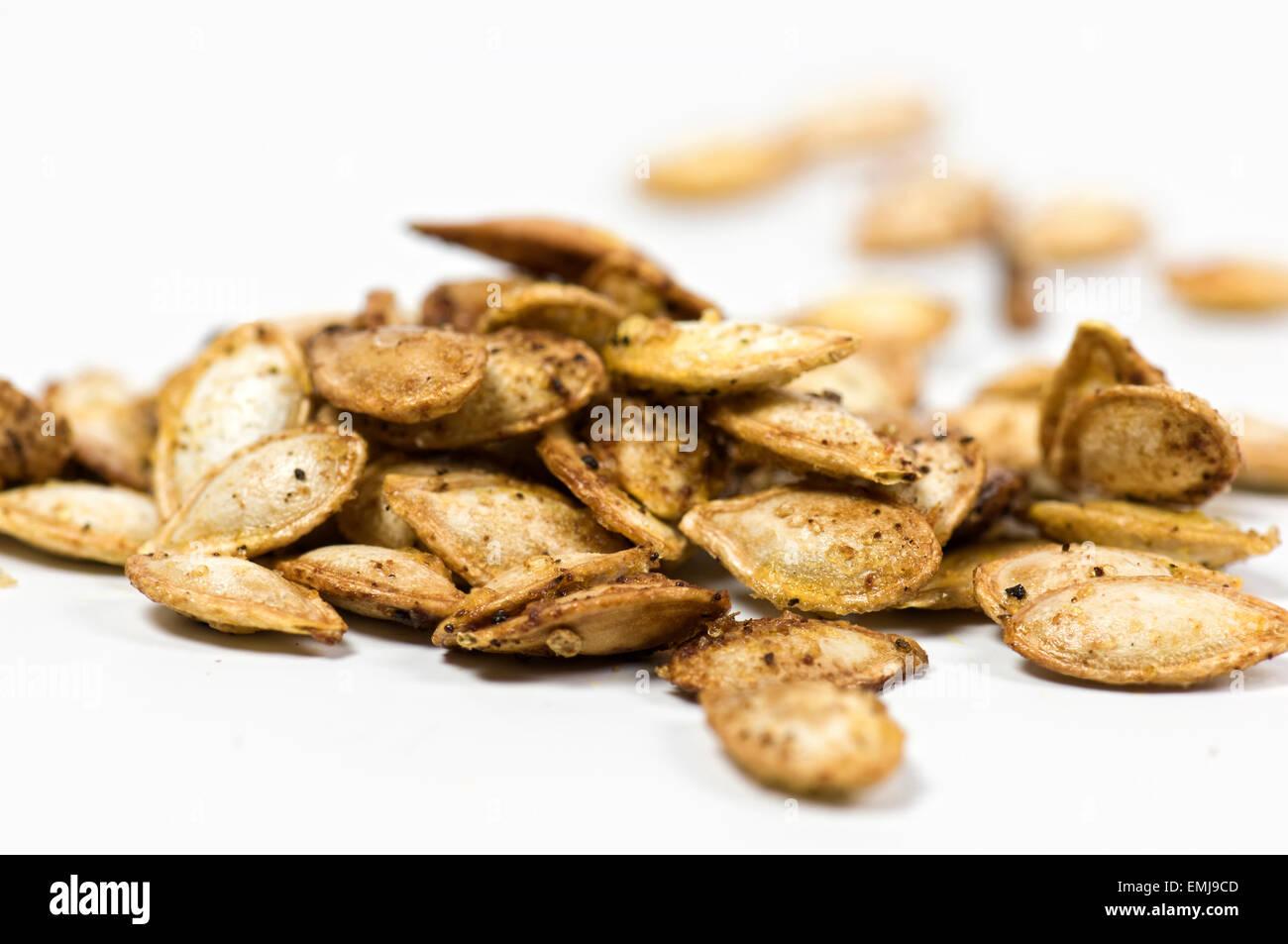 Arrosto di zucca semi su sfondo bianco Immagini Stock