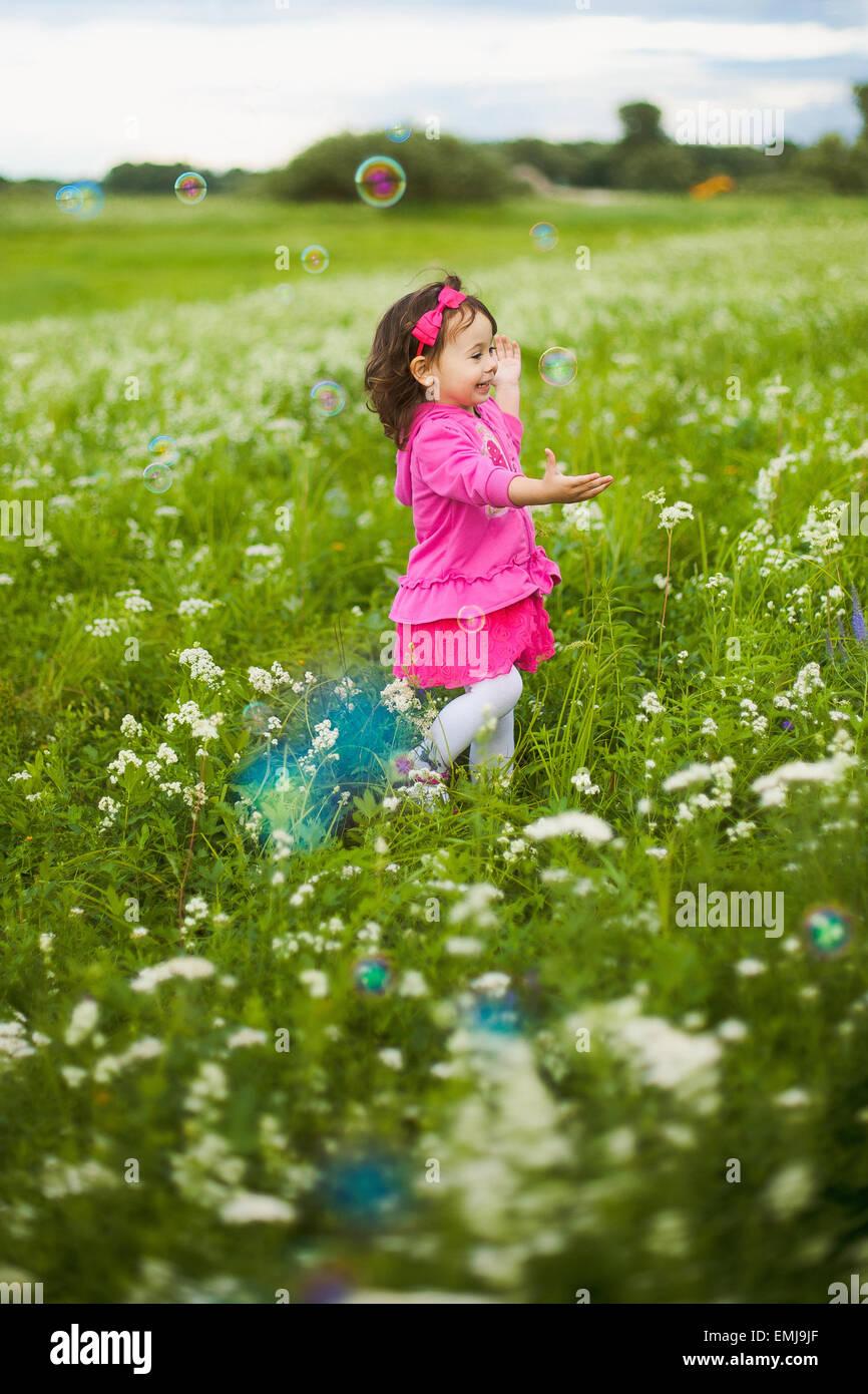 Bella ragazza spensierate giocando all'aperto in campo con alta erba verde. piccolo bambino di scappare da bolle Immagini Stock