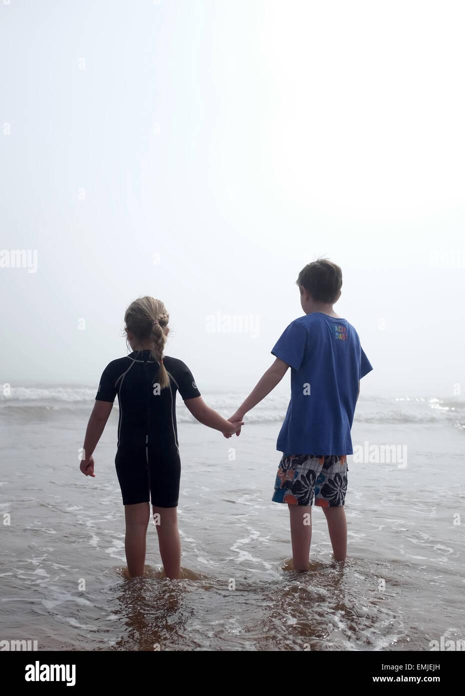 Un ragazzo e una ragazza tenendo le mani si affacciano verso il mare in un giorno di nebbia Immagini Stock