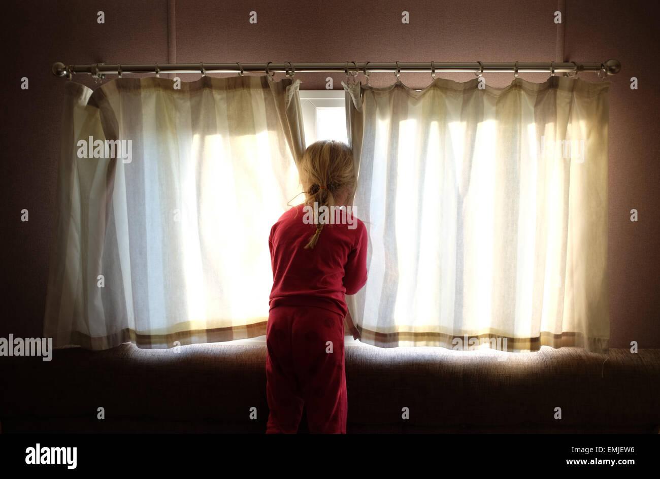 Una sonnolenta giovane ragazza in pigiama apre le tende a guardare fuori dalla finestra all'inizio di un nuovo Immagini Stock