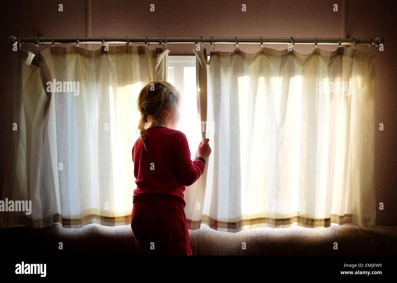 Una sonnolenta giovane ragazza in pigiama apre le tende a guardare fuori dalla finestra all'inizio di un nuovo giorno Foto Stock