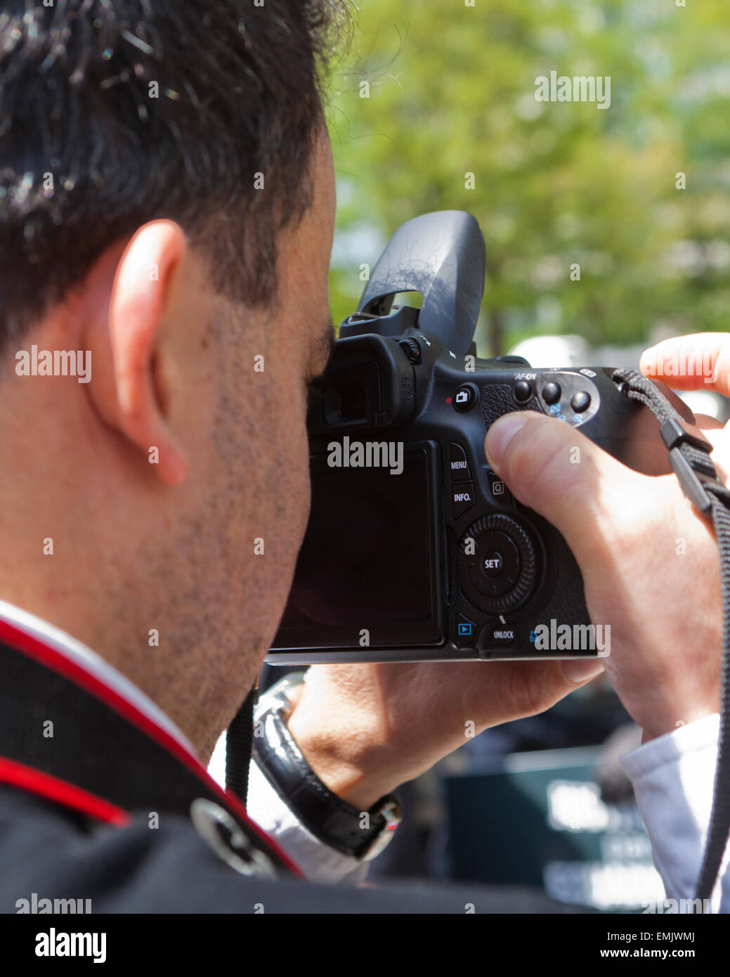 Uomo che guarda attraverso il mirino della fotocamera dSLR - USA Immagini Stock