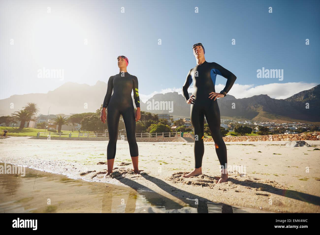 Ritratto di un determinato maschio e femmina triatleti guardando in lontananza. Giovane uomo e donna in piedi presso Immagini Stock