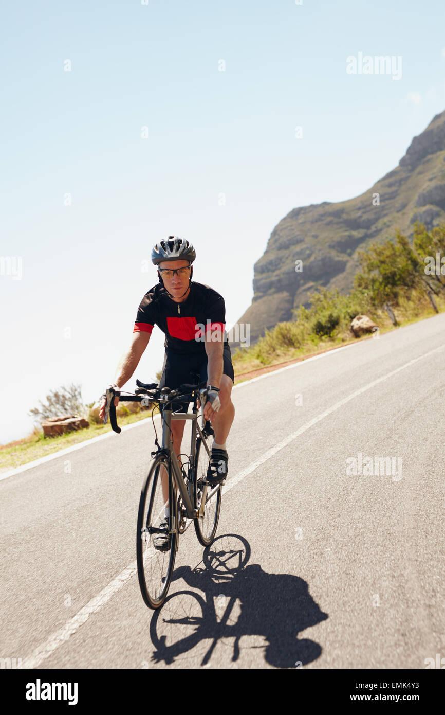 Inquadratura di un ciclista maschio cavalcare giù lungo una strada di campagna. Triatleta escursioni in bicicletta Immagini Stock
