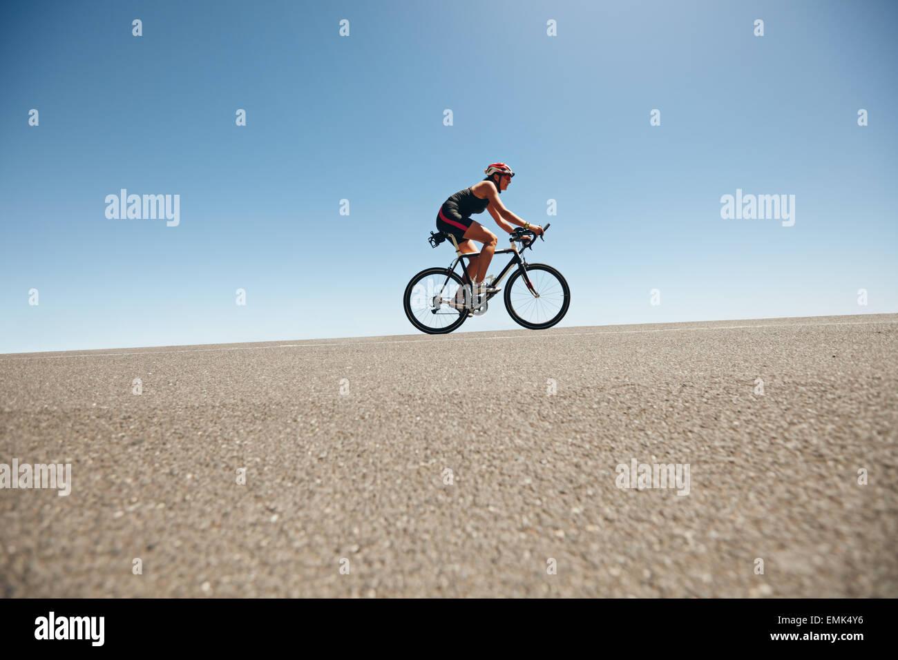 Ciclista femmina su una strada di campagna di formazione per il triathlon. Giovane donna Bicicletta Equitazione Immagini Stock