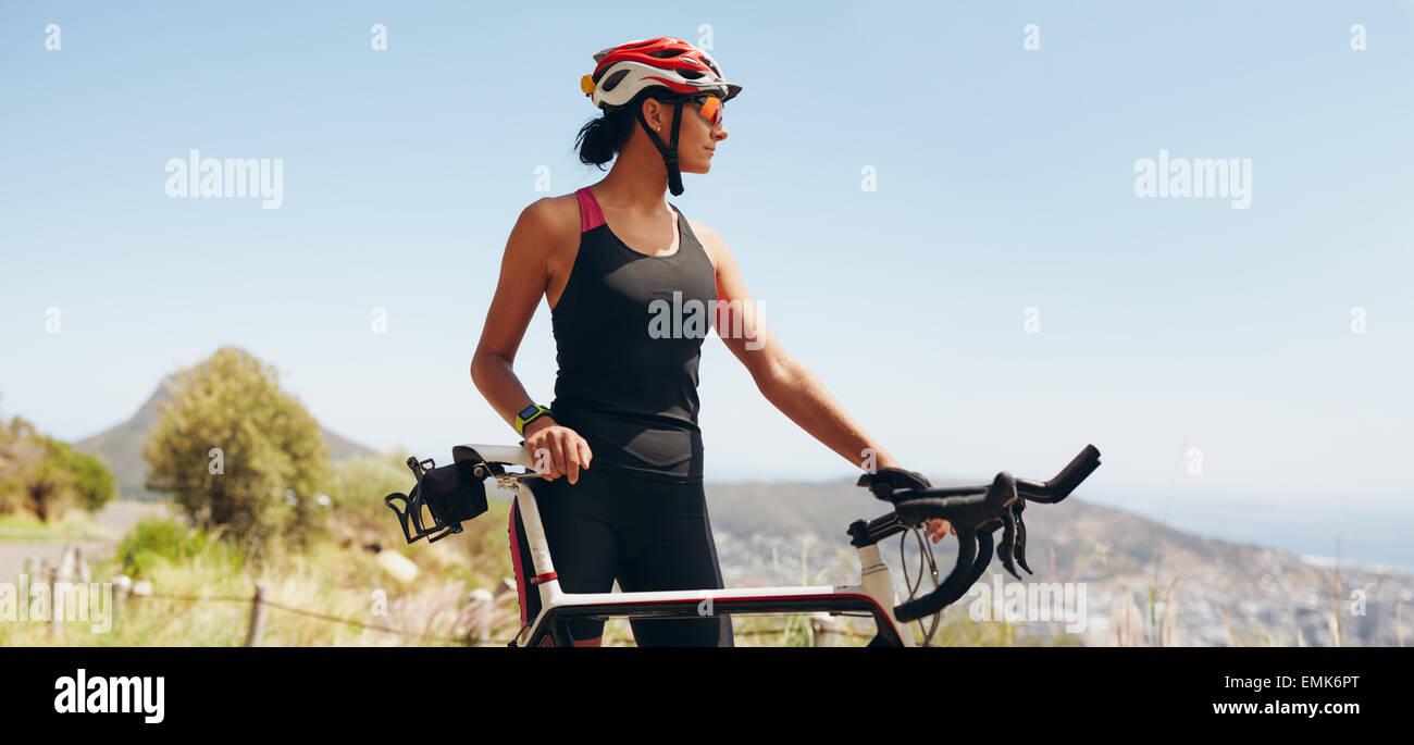 Immagine di determinata ciclista femmina che guarda lontano. Montare la donna che indossa abbigliamento sportivo Immagini Stock