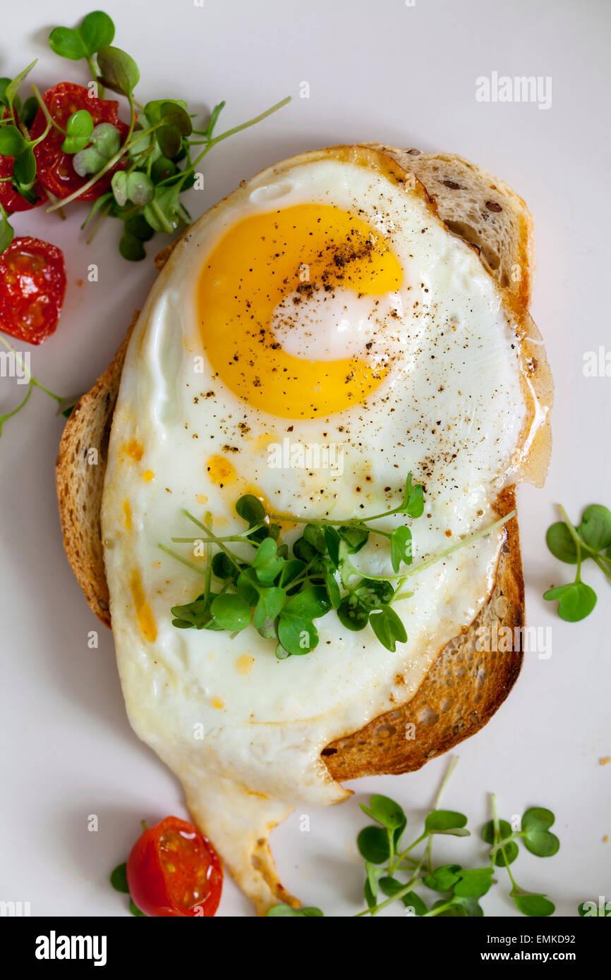 La prima colazione, le uova sul pane tostato con pomodorini e crescione Immagini Stock