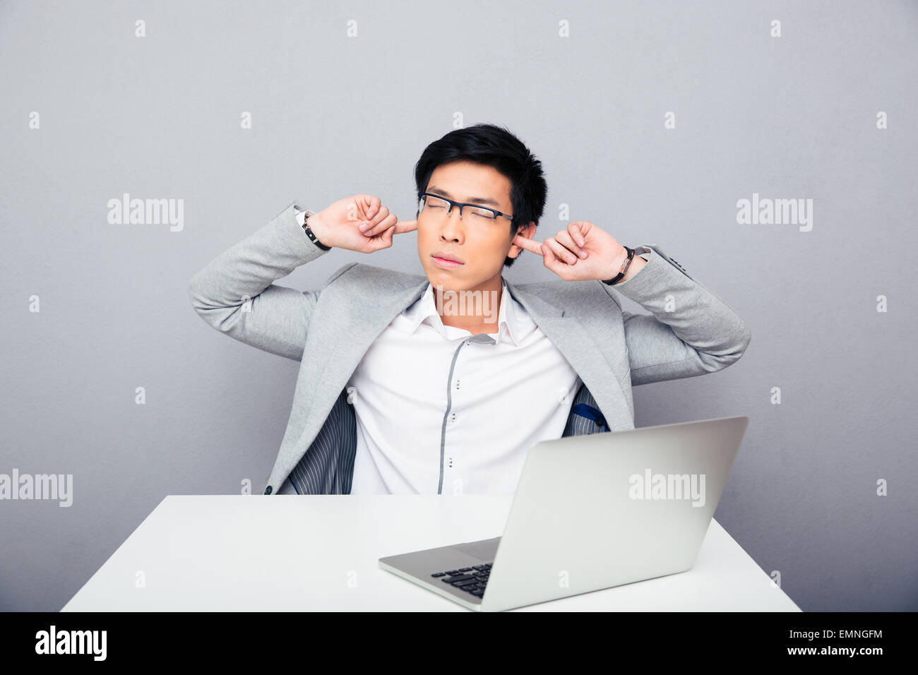 Bello imprenditore asiatici seduti a tavola e che copre le sue orecchie su sfondo grigio Immagini Stock