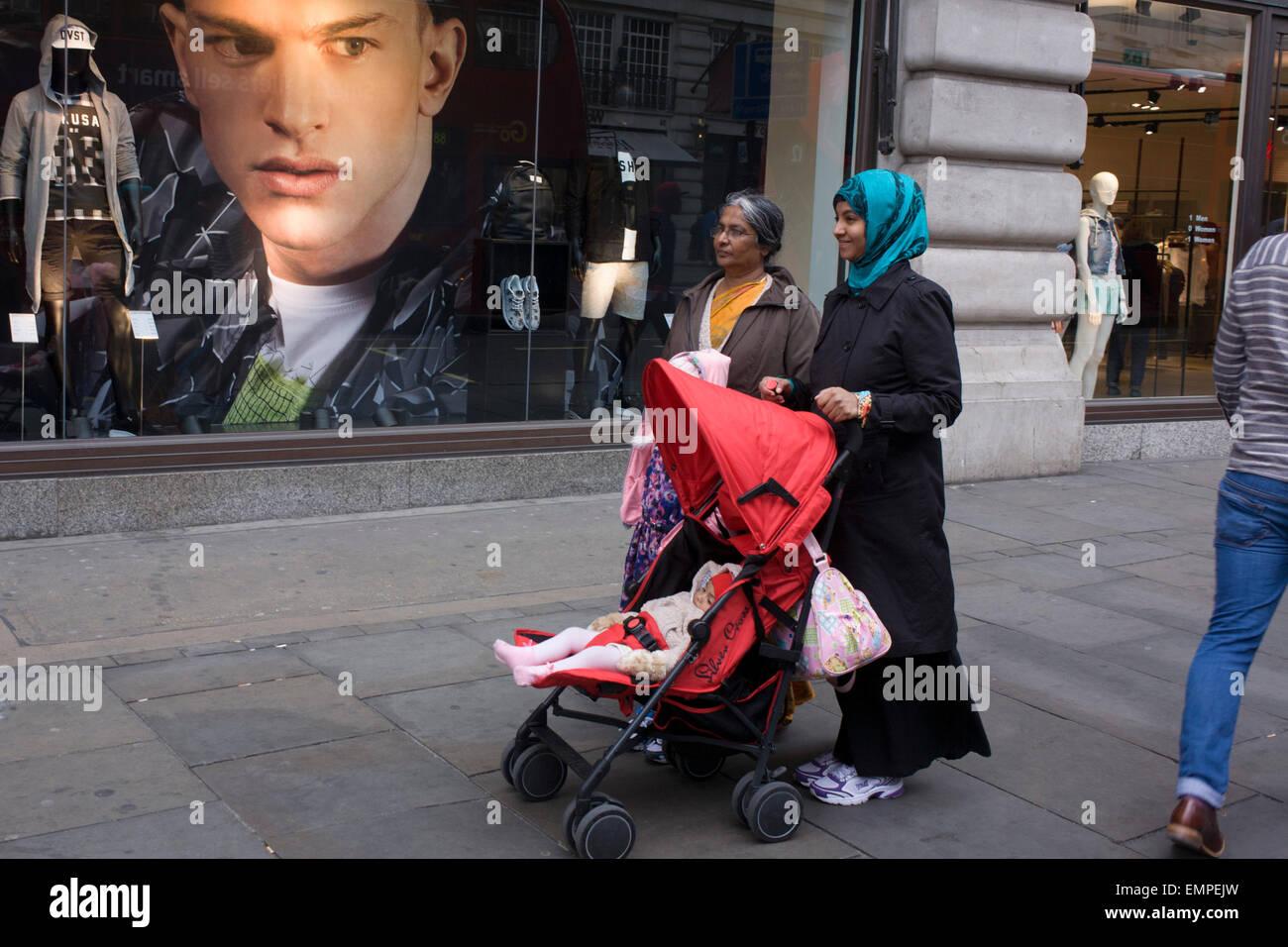 Mussola di famiglia e una grande immagine di un modello maschile nella finestra di abbigliamento rivenditore H&M Immagini Stock