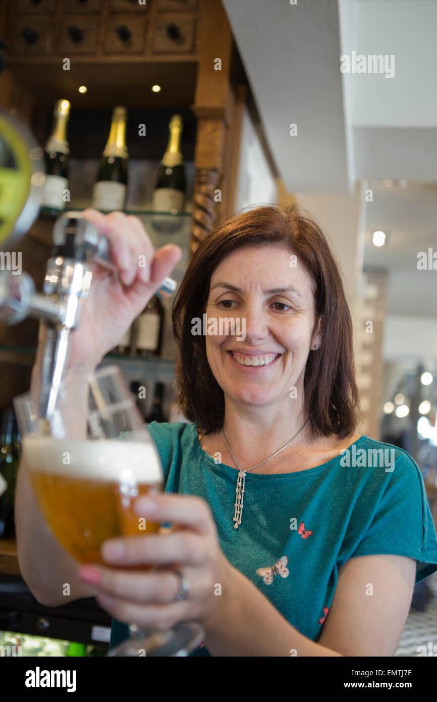 Una donna dietro un bar tirando una pinta di birra lager mentre sorridente Immagini Stock