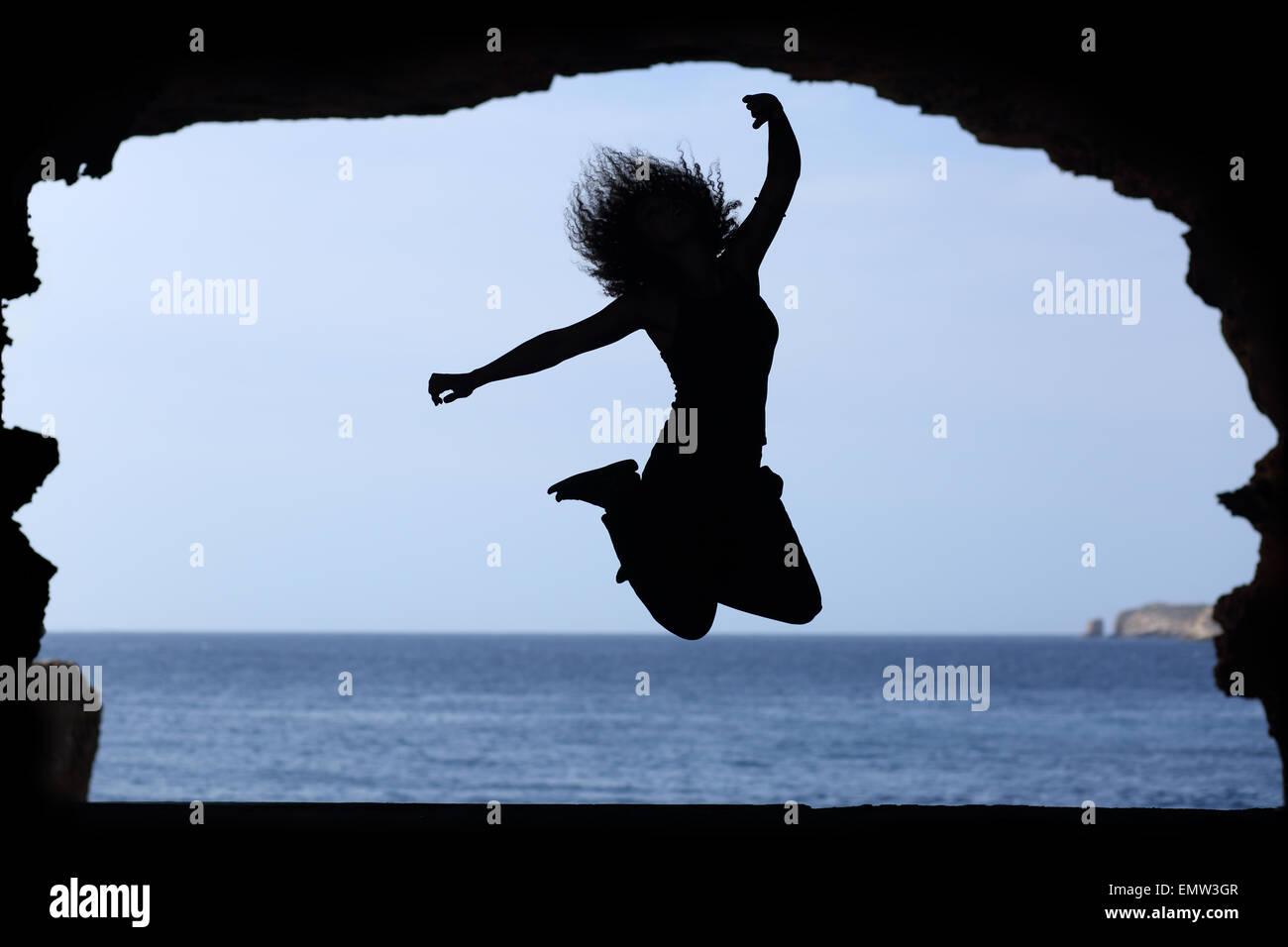 Silhouette Di Donna Salta Sulla Spiaggia Con Il Mare In Sottofondo
