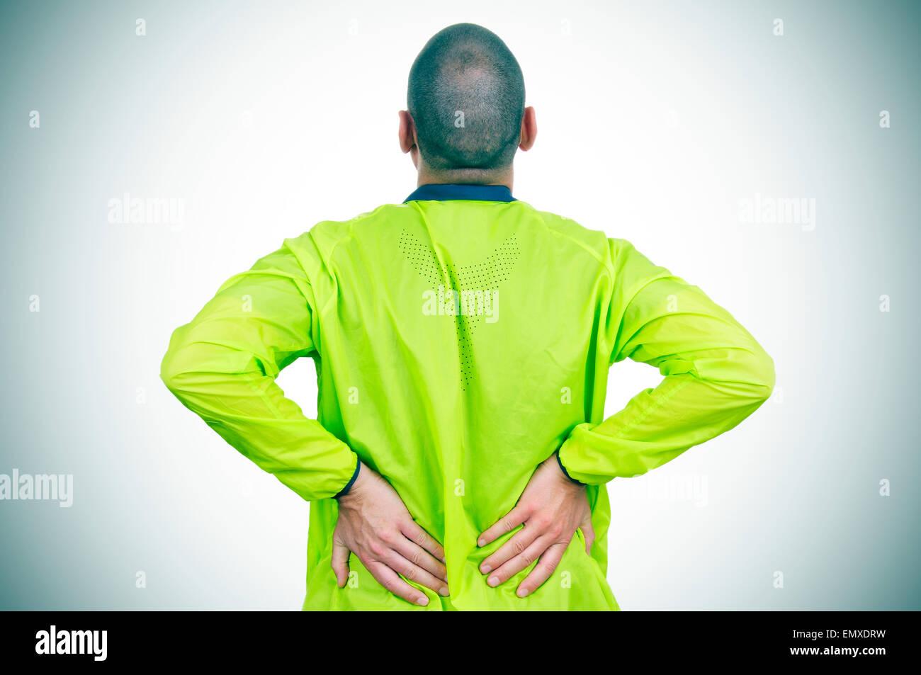 Un giovane sportivo caucasica indossando indumenti sportivi con le sue mani nel suo ritorno a causa della sua bassa Immagini Stock
