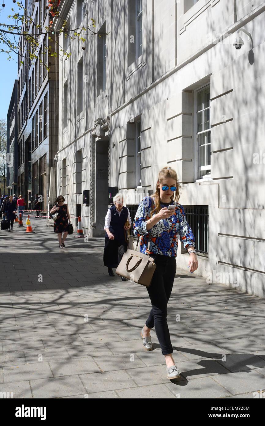 Giovane donna bionda con il designer borsetta e utilizzando un I-phone mentre camminando sul marciapiede in Londra Immagini Stock