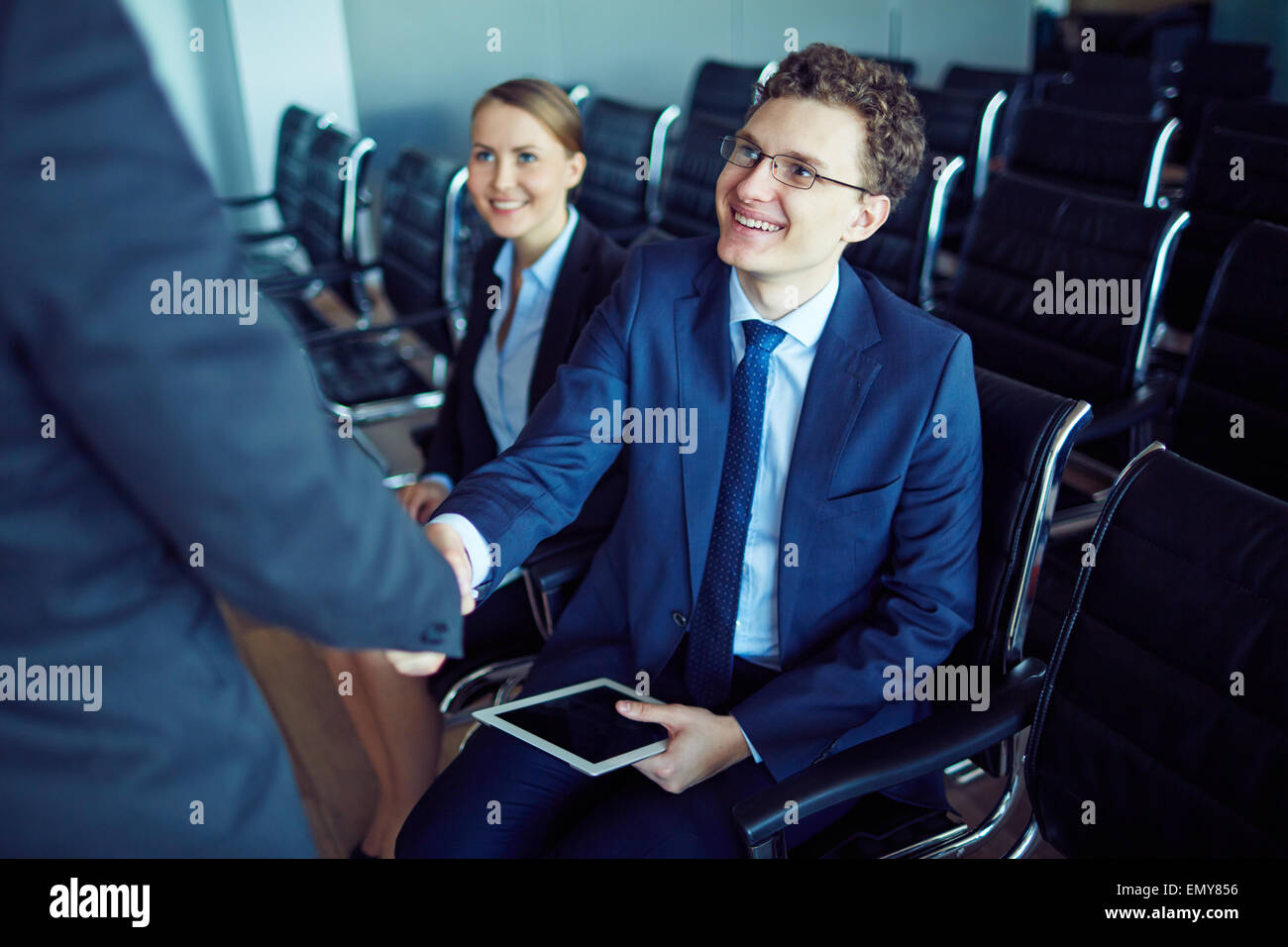 Dipendente di sesso maschile in tuta e occhiali saluto il suo partner durante la conferenza Immagini Stock