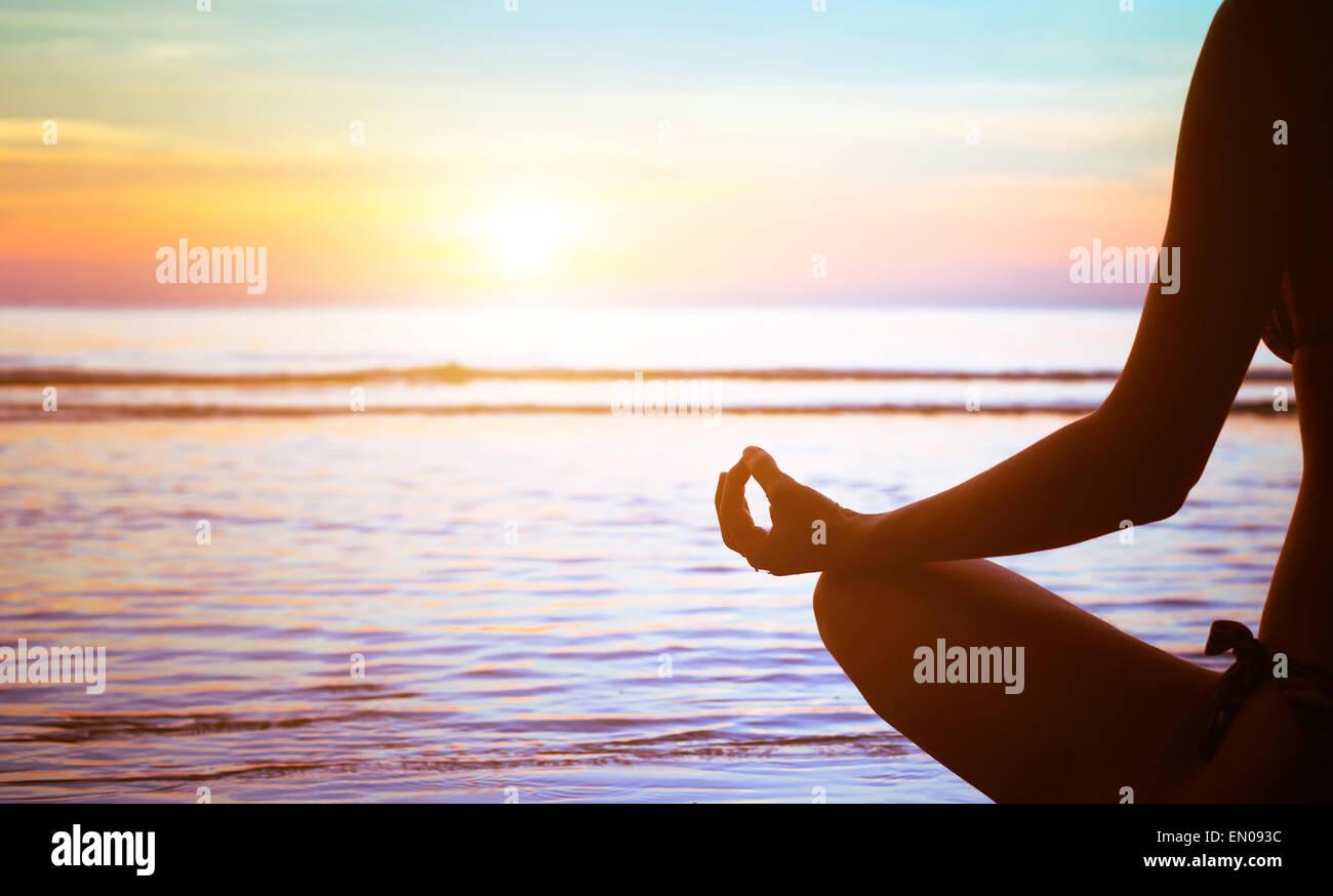 Concetto di meditazione, yoga pratica sulla spiaggia al tramonto Immagini Stock