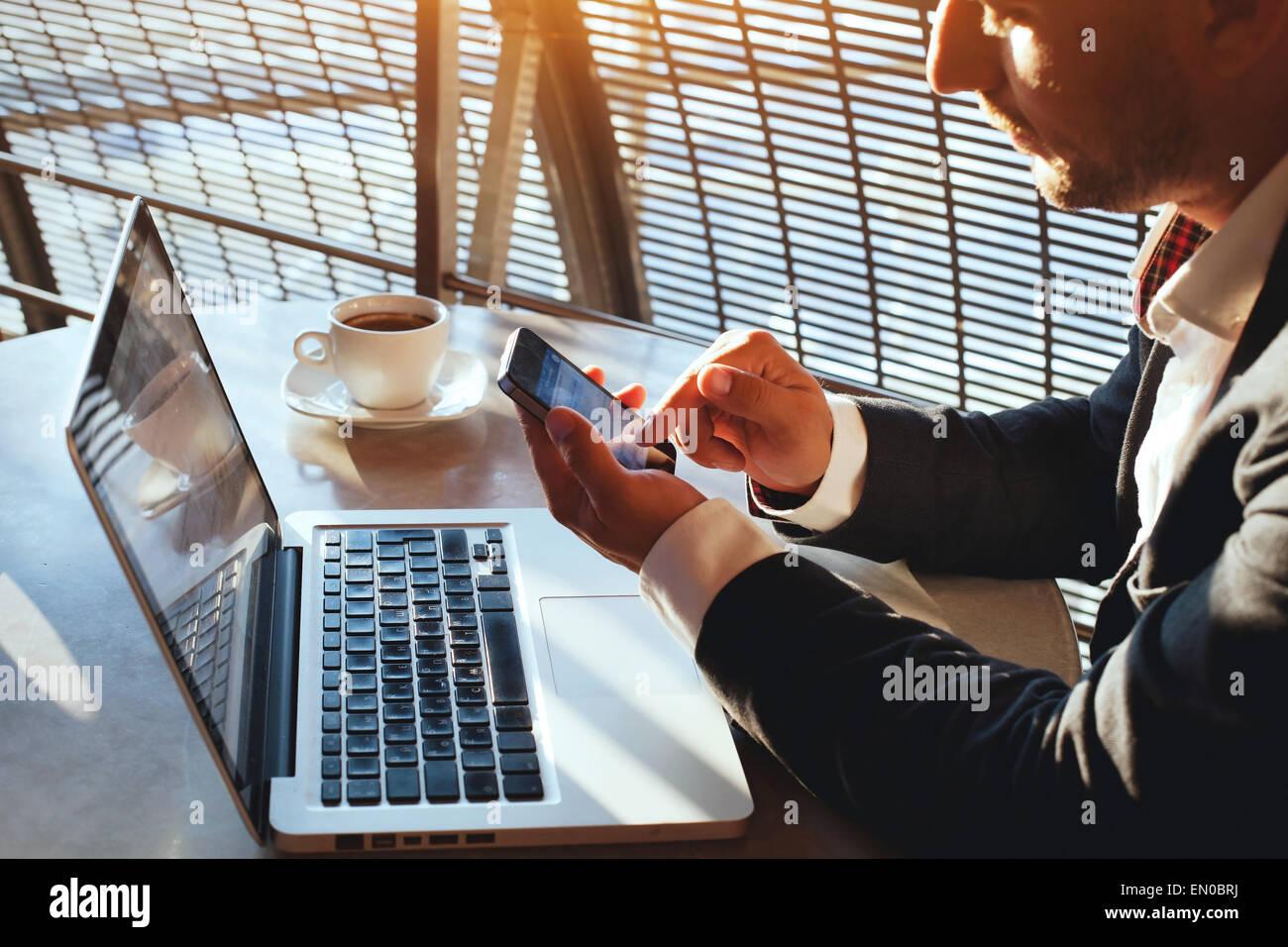 Uomo d affari con internet su smart phone e il computer portatile Immagini Stock