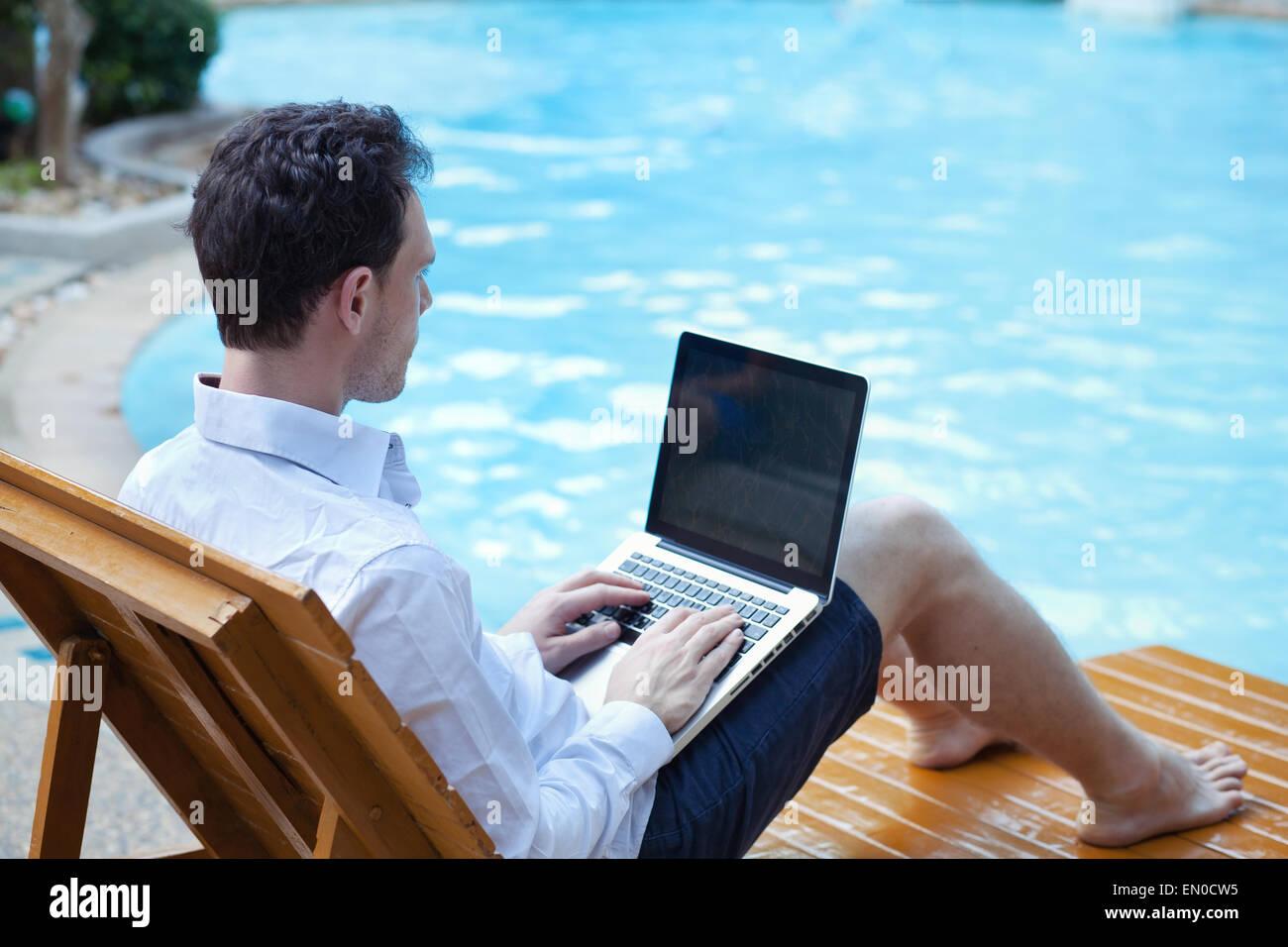 Uomo d affari con computer portatile in hotel di lusso vicino alla piscina Immagini Stock