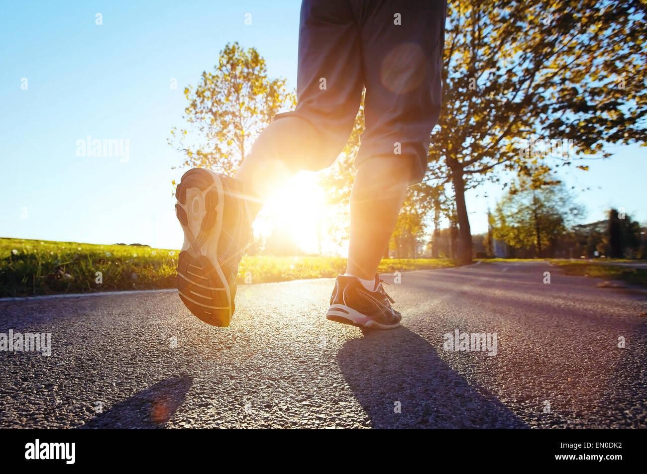 Close up piedi di runner al tramonto Immagini Stock