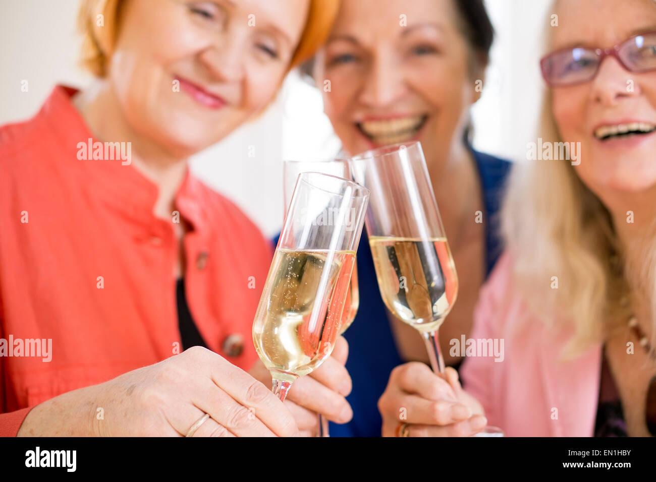 Tre sorridente Mom amici Tossing bicchieri di champagne per celebrare la loro amicizia. Catturate in macro. Immagini Stock