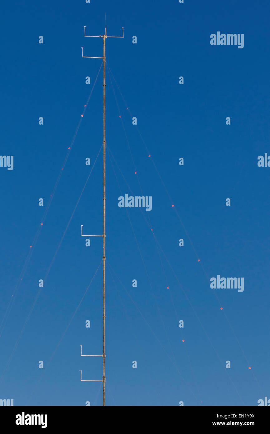 Vista della parte superiore di un montante di anemometro, con deflettori, contro un cielo blu, Cambridgeshire. Eretto Immagini Stock