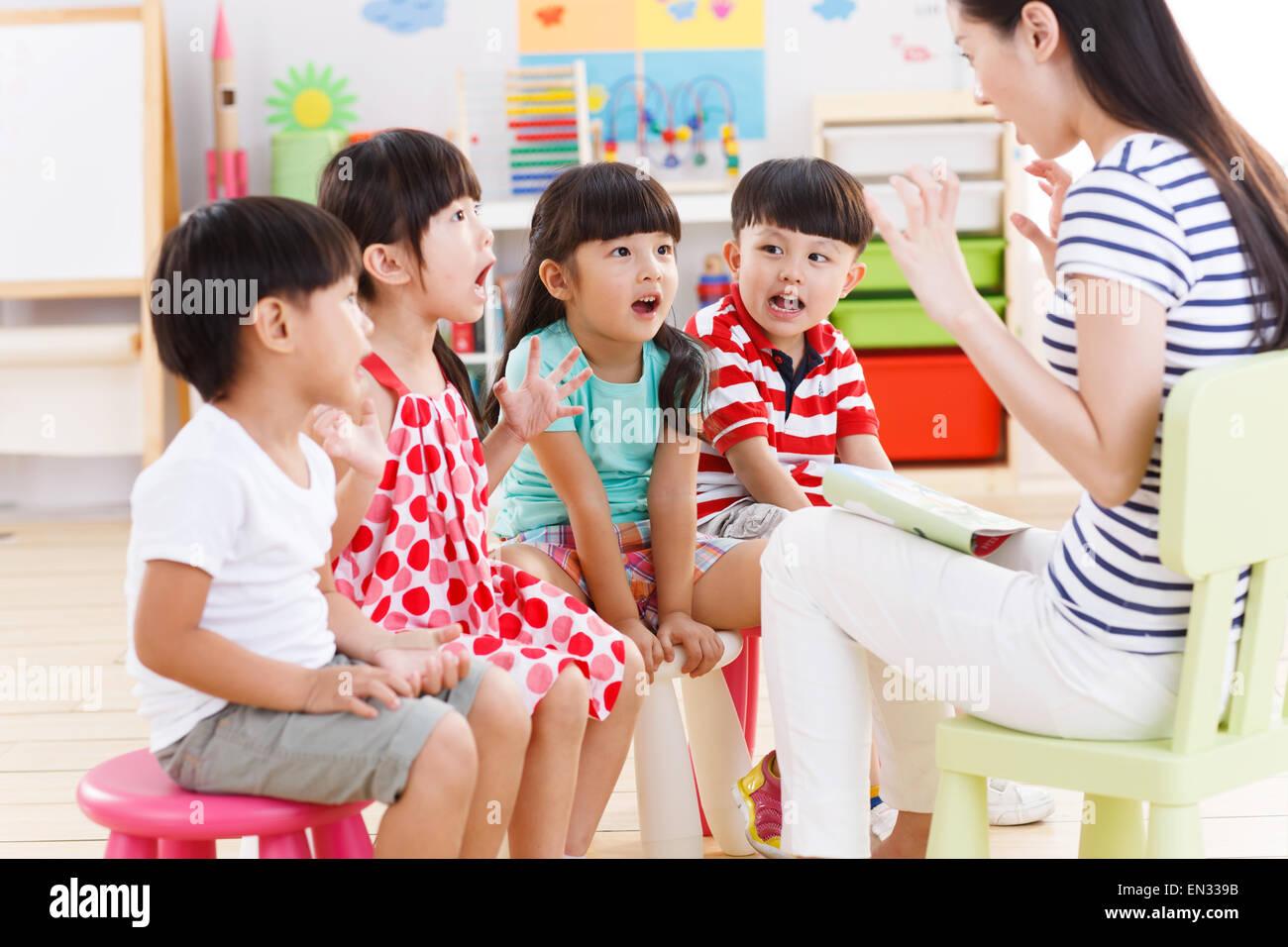 L'insegnante di scuola materna si racconta una storia per bambini Immagini Stock